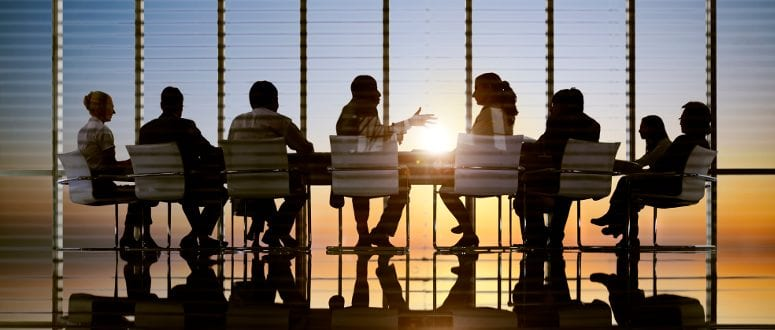 A group of people work around a table in an office at sunset.