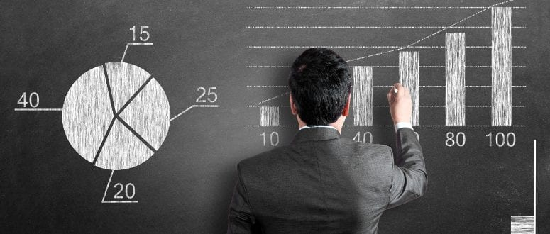 A person in a suit draws a graph on a blackboard.
