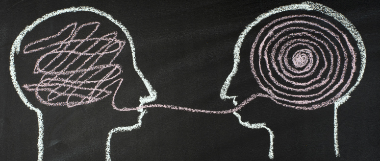 Conversational intelligence. A chalk outline of two heads facing each other. The brain on the left contains a disorganized line. The line extends out the head's mouth and to the mouth of the head on the right. It then forms a spiral in the right head's brain.