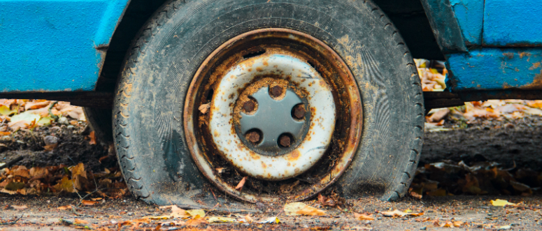 A close-up of a flat tire on an old car.