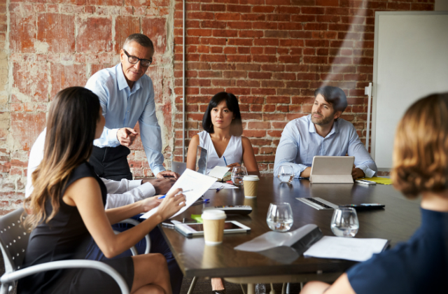 A group of six working people sit and stand around a table and communicate.