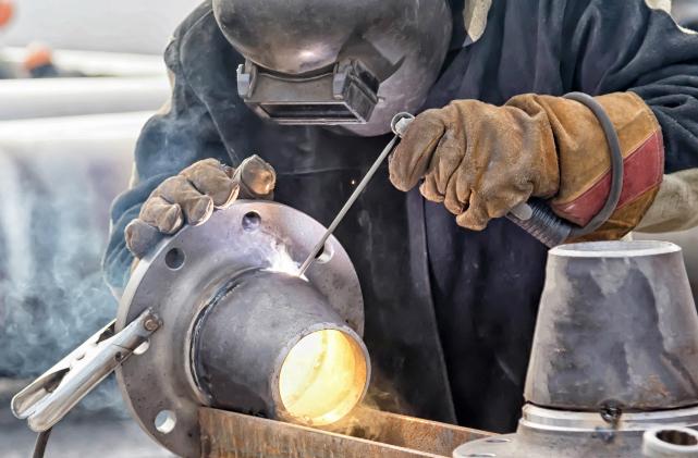 A welder in full P P E welds a piece of metal.