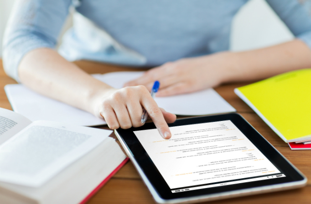 A woman sits at a table holding a pen and scrolling on a tablet. An open book and notepad are also on the table.