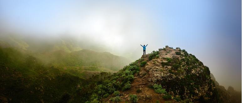 A person near the peak of a mountain raising their hands above their head.