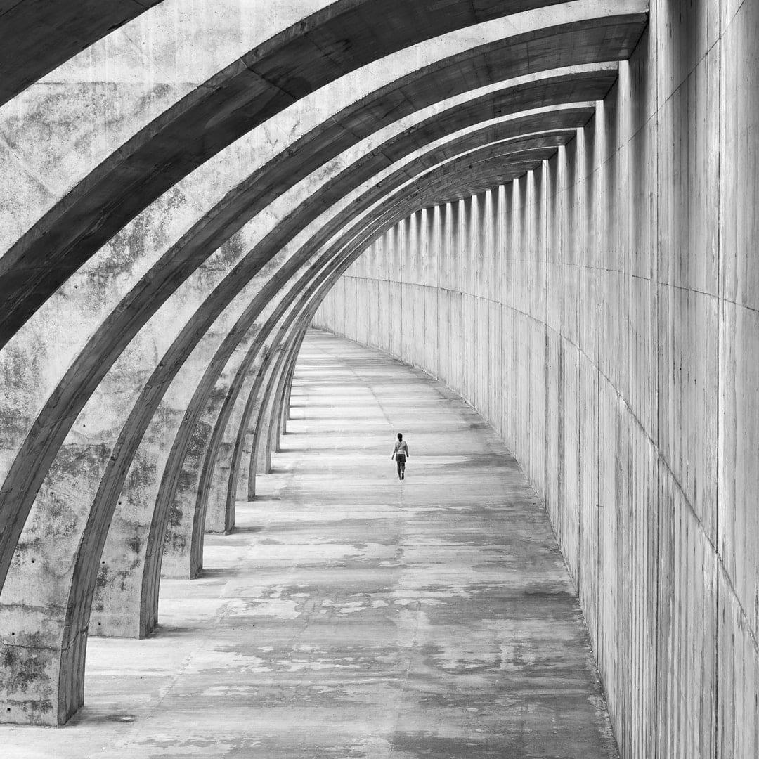A person walks along an enclosed bridge.