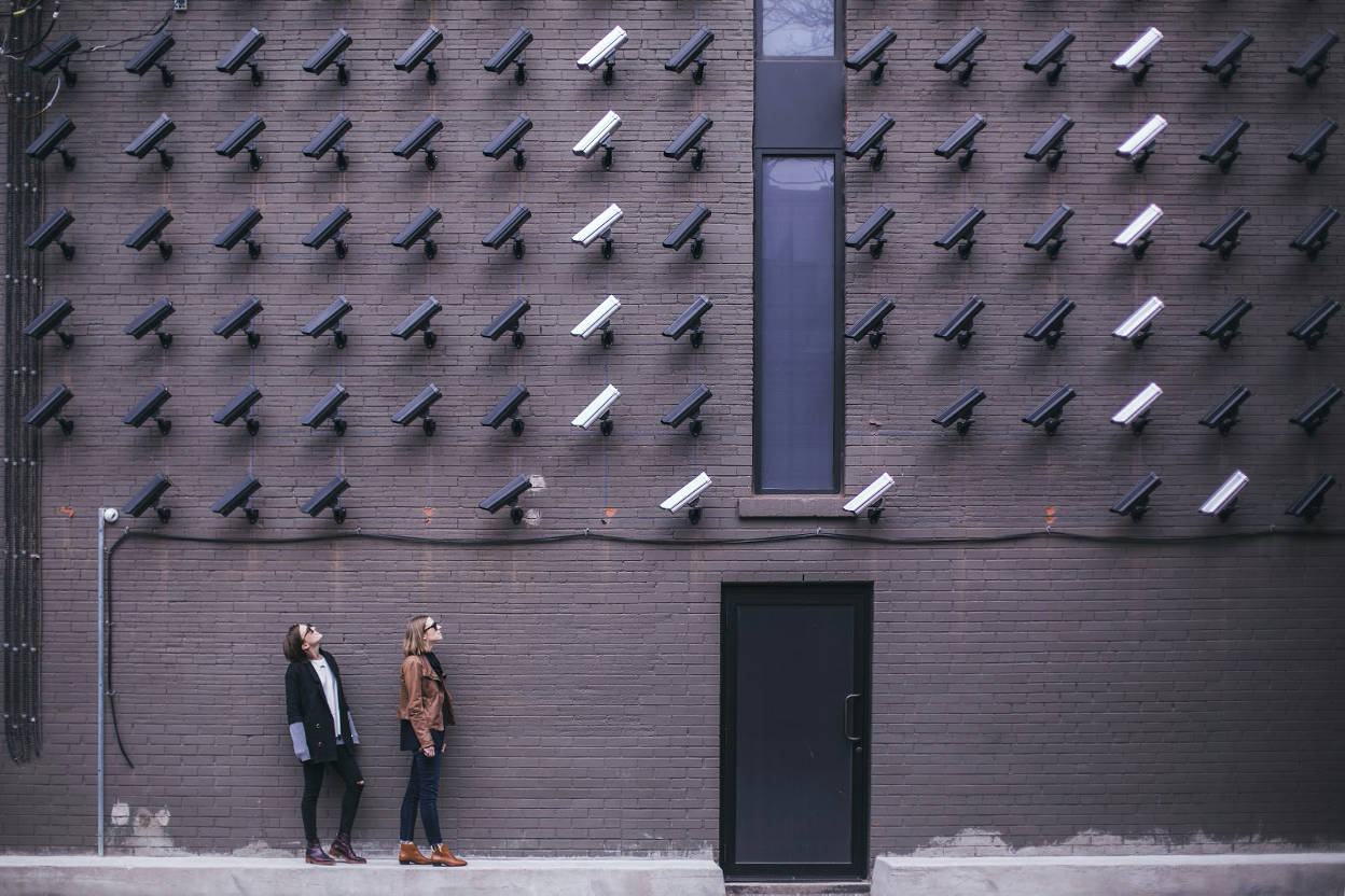A brick wall with over 70 mounted C C T V cameras focused downward. Two people stand on the sidewalk and look up at them.