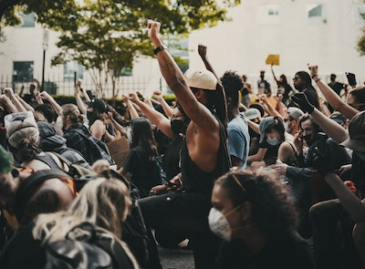 A group of people, most with one arm raised with the hand in a fist. Many of the people wear face masks.